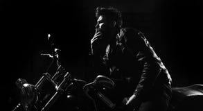 Noc setkarza pojęcie Mężczyzna z brodą, rowerzysta w skórzanej kurtki obsiadaniu na motorowym rowerze w ciemności, czarny tło mac zdjęcia royalty free