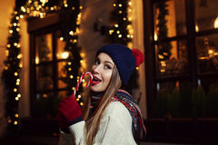 Noc uliczny portret uśmiechniętej pięknej młodej kobiety cukierku zjadliwa trzcina Dama jest ubranym klasyczną zimę dziającą odzi Zdjęcie Royalty Free