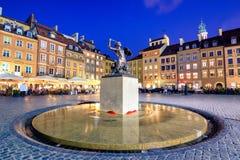Noc widok brązowa statua syrenka na Starym Grodzkim Targowym kwadracie Warszawa, otaczającym kolorowymi starymi domami Zdjęcia Stock