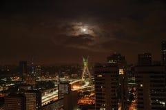 Noc widok miasto linia horyzontu z mostem, budynki pod chmurnym i księżyc w pełni w mieście São Paulo obraz stock