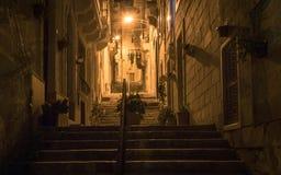 Noc widok na alleyway iść na piętrze, światła i poręcz zakrywający starymi domowymi przodami Niektóre kwiaty w garnku Odzieżowy o zdjęcie royalty free