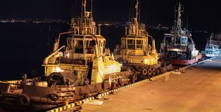 Noc widok trzy tugboats w ładunku porcie zdjęcie stock