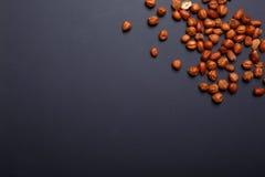 Nocciole, dadi utilizzati per produrre pralina ed anche utilizzati congiuntamente a cioccolato su un fondo di violazione, spazio  fotografia stock libera da diritti