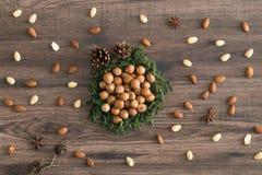 Nocciole in muschio con i coni, badian e le mandorle su un fondo di legno fotografia stock