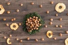 Nocciole in muschio con le mele badian e secche su un fondo di legno fotografia stock libera da diritti
