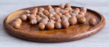 Nocciole su un piatto di legno sulla tavola fotografie stock libere da diritti