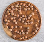 Nocciole su un piatto di legno sulla tavola Vista superiore fotografie stock libere da diritti