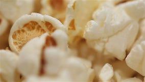 Noccioli schioccati caldi che girano sul piatto, tempo di film, alti alimenti del popcorn di caloria archivi video
