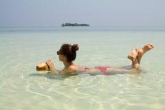 Noce di cocco bevente della ragazza graziosa che si trova nel mare Fotografie Stock