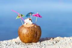 Noce di cocco con cannuccia, gli ombrelli ed i fiori Fotografia Stock