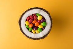 Noce di cocco con le caramelle variopinte fotografie stock libere da diritti