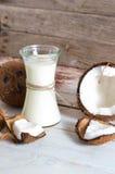 Noce di cocco con olio di cocco in barattolo su fondo di legno Immagini Stock