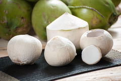 Noce di cocco della sbucciatura sulla stuoia con il fondo verde della noce di cocco Fotografie Stock