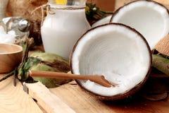 Noce di cocco e latte, Cochi dell'olio per alimento sano organico e bellezza Fotografia Stock
