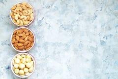 Noce di macadamia matta assortita, mandorle, anacardio in una ciotola sulla disposizione piana del fondo strutturato con lo spazi Fotografie Stock