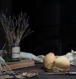 Noch Leben 1 Birne, alte Bücher und ein Bündel Lavendel auf dunklem Hintergrund Stockfoto