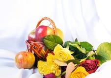 Noch Leben mit dem Korb der Äpfel und der Rosen lizenzfreie stockbilder