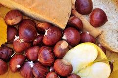 Noch Leben mit Kastanien, Apfel und Brot Lizenzfreie Stockbilder
