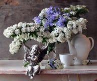 Noch Leben mit weißen Blumen und Amor Stockfotos