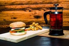 Noch lebens- Hamburger mit Teefranzosepresse stockbilder