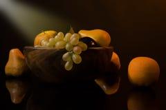 Noch-Lebensdauer mit Frucht in einem hölzernen Teller lizenzfreie stockfotos