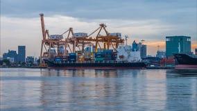 Noche al día de nave de la carga del cargo del envase con el puente de trabajo de la grúa en astillero metrajes