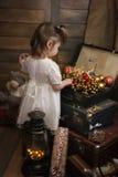 Noche antes del pequeño bebé de la Navidad que se sienta en el piso y el juego Foto de archivo libre de regalías