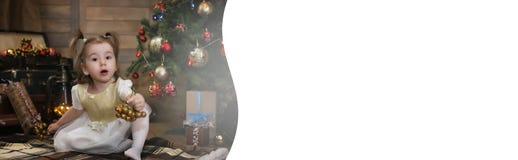 Noche antes del pequeño bebé de la Navidad que se sienta en el piso y el juego Fotografía de archivo