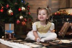 Noche antes del pequeño bebé de la Navidad que se sienta en el piso y el juego Imagenes de archivo