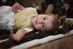 Noche antes del pequeño bebé de la Navidad que se sienta en el piso y el juego Imagen de archivo