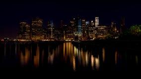 Noche del horizonte de New York City con la reflexión Fotografía de archivo libre de regalías