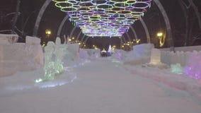 Noche del invierno en el parque del hielo Pueblo de la nieve La gente y el bebé caminan en ciudad del hielo durante las nevadas J