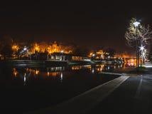 Noche en el parque de Timisoara por el río con reflexiones y el puente fotografía de archivo
