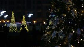 Noche festiva en el cuadrado central de la ciudad grande adornado con los árboles agradables del Año Nuevo almacen de video