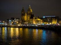 Noche hermosa en Amsterdam Iluminación de edificios cerca del agua en el canal Fotos de archivo