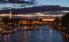 Noche hermosa Par?s, torre Eiffel chispeante, puente Pont des Arts sobre el r?o el Sena y barcos tur?sticos francia foto de archivo