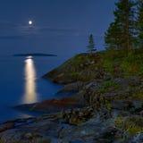 Noche iluminada por la luna en la orilla pedregosa del lago ladoga Imagenes de archivo