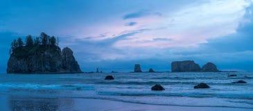 Noche nublada en una playa de la Costa del Pacífico con las pilas del mar fotografía de archivo