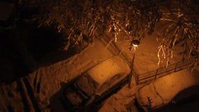 Noche que nieva en el estacionamiento