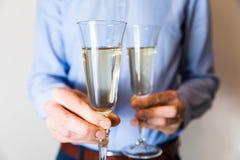 Noche romántica de la fecha de día de San Valentín, hombre hermoso que sostiene dos vidrios del champán para los pares foto de archivo