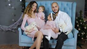 Noche Vieja, padres jovenes con los niños y perritos mullidos blancos en el sofá en la sesión de foto almacen de video