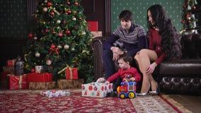 Nochebuena, la familia que se sienta al lado del árbol de navidad, que se adorna con costoso Su pequeño hijo almacen de metraje de vídeo