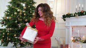 Nochevieja, la muchacha da un regalo de la Navidad, cerca del árbol de navidad y de la chimenea en los cuales las velas encendida almacen de video