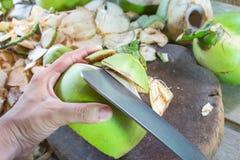 Noci di cocco della sbucciatura con lo spezzettamento del coltello a pezzi Fotografia Stock