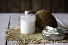 Noci di cocco e olio di cocco in un vaso del metallo Priorit? bassa di legno immagine stock