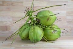 Noci di cocco verdi su fondo di legno Fotografia Stock