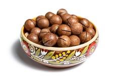 Noci di macadamia sbucciate organiche fresche in ciotola ceramica isolata su bianco immagine stock