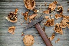 Noci incrinate e martello su vecchio fondo di legno Fotografia Stock