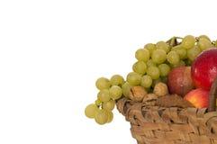 Noci, mele ed uva in un cestino di vimini Fotografia Stock Libera da Diritti