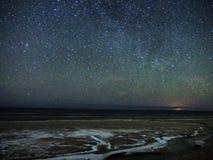 Nocne niebo śnieg na dennym wybrzeżu i gwiazdy fotografia stock
